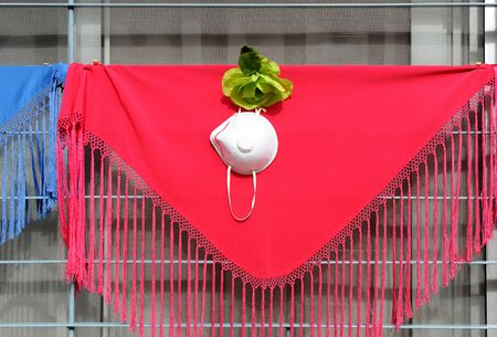 Personal protection face mask with FFP2 particle filtration on a red shawl. Time of Covid-19 in Seville, Spain