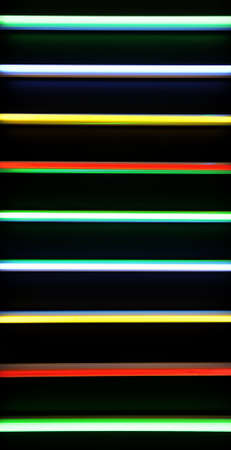 Colored fluorescent tubes placed horizontally on a black opaque background