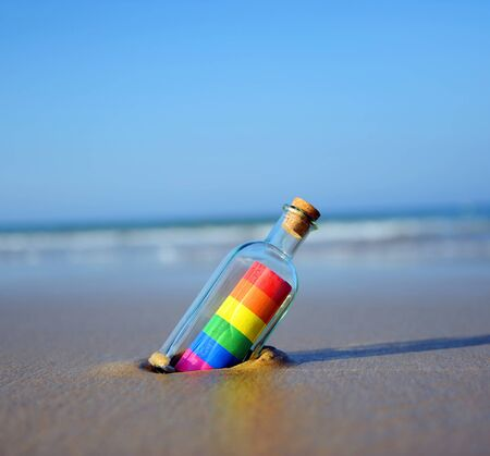 Gay pride message in a bottle on the seashore, equal rights concept