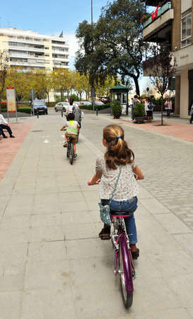 Family bike ride. Cycling through Los Remedios neighborhood in Seville, Andalusia, Spain Editorial