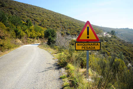 Mountain road with danger warning traffic sign: movement of heavy machinery Galicia Spain Standard-Bild