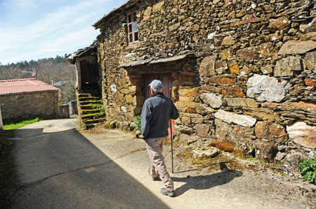 Senior man walking through the village of As Eiras on the Camino de Santiago towards Laza, Orense province, Spain Editorial