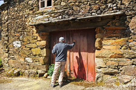 Senior man knocking on the door of a house in the village of As Eiras on the Camino de Santiago to Laza, Orense province, Spain