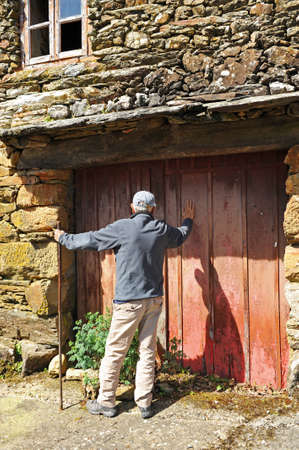 Man knocking on the door of a house in the village of As Eiras on the Camino de Santiago to Laza, Orense province, Spain