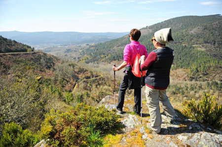 Two women hikers on the mountains of Laza, Camino Sanabres from Campobecerros towards the town of Laza, Orense province, Spain