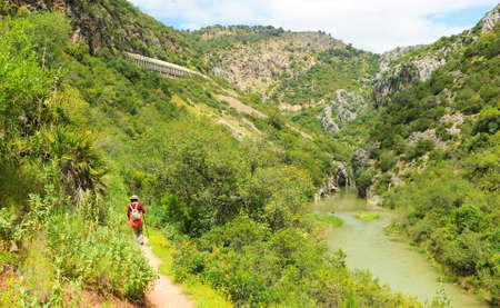 Woman hiking in the Guadiaro river near the Canyon of the Buitreras -Canon de las Buitreras-, famous gorge located at the Alcornocales Natural Park, province of Malaga, Andalusia, Spain