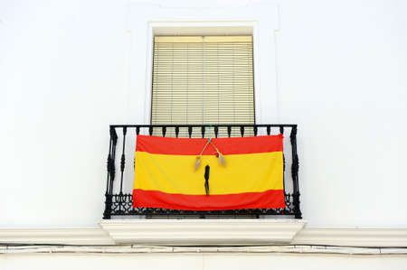 Balcony of a whitewashed house in a southern Spanish town with the flag of Spain with a black ribbon of mourning in memory of those who died of the Coronavirus Covid 19