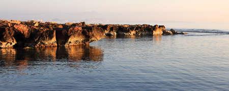 Beautiful sunrise on the coast with the sun illuminating the rocks and the sea
