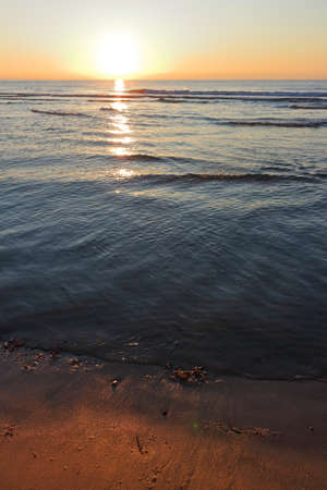 The sunrise sun over the ocean horizon from the shore of the beach 스톡 콘텐츠