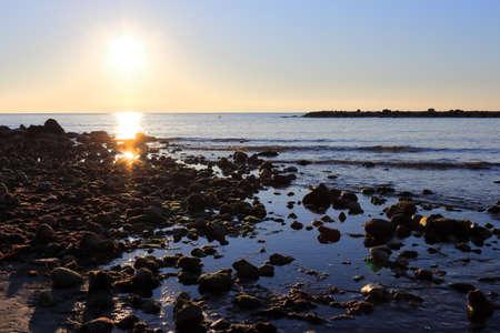 The sunrise sun over the ocean horizon from the shore