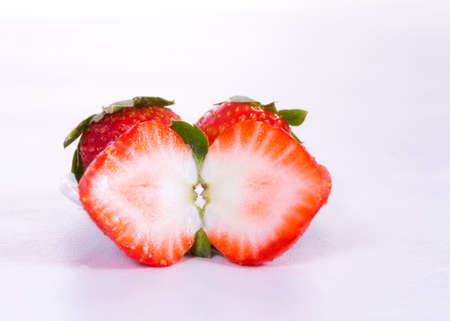 two and a half: a strawberry chopped in half and two strawberries behind this more, all on white background Stock Photo