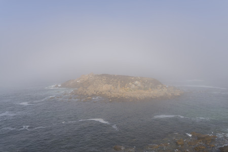 inclement weather: Small island in a foggy day.