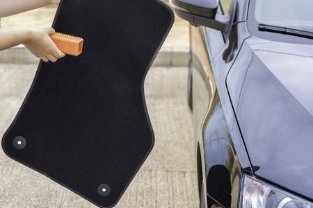 Cleaning car mat.