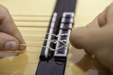 Knotting the string of a guitar. Stock Photo