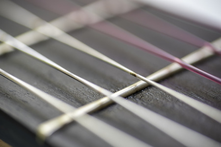 Wear the strings of a guitar.