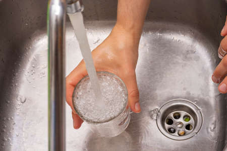 Filling a glass of water. Stock Photo