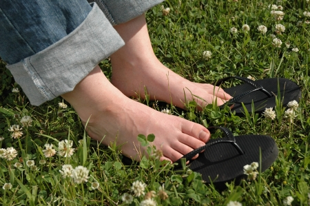 Woman Feet in Grass with White Flowers photo