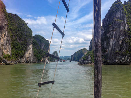 Beautiful limestone karsts and boats in Ha Long Bay, Vietnam, seen through the rigging of a sait boat