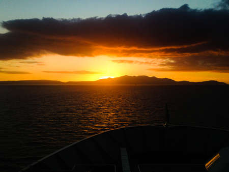 Sunrset over the Isle of Arran in Scotland from the ferry that crosses to the island