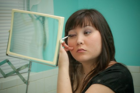 primp: Woman putting on her makeup in the mirror.