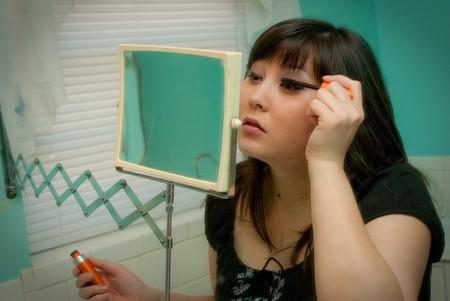 primp: Donna mettendo il suo trucco allo specchio. Archivio Fotografico