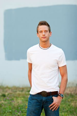 A male model looks directly at the camera with his hands in his pockets while wearing a white tee shirt.