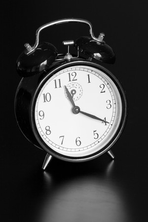 A wind up clock on a black table.  The clock is old and scratched up. Stock Photo