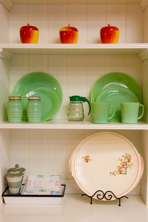Detail photo of dishes and glassware in a cabinet.