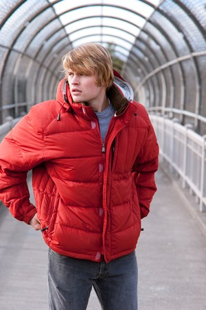 A male model with his hands at his sides on a covered walking bridge wearing a bright red jacket.