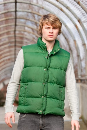 A man in a bright green puffy vest walks toward the camera during a photo shoot in a walking bridge that is covered in rusted metal.