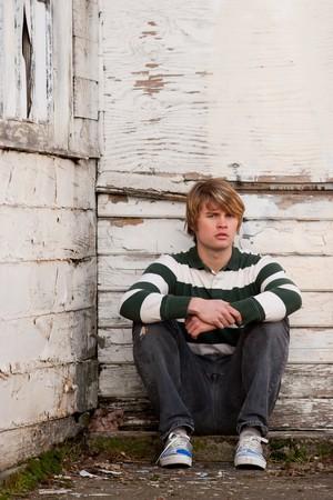 Een mannelijk model zit tegen een oude muur met peeling paint terwijl u eenzaam en radeloos.