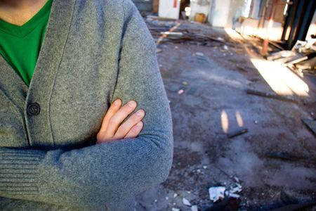 confrontational: A man wearing a sweater folds his arms at a dirty warehouse building. Stock Photo