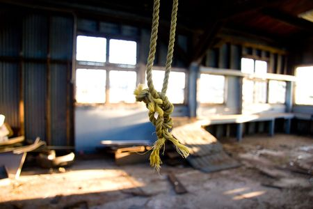 rafters: A rope dangles from the rafters at an old rundown warehouse building.