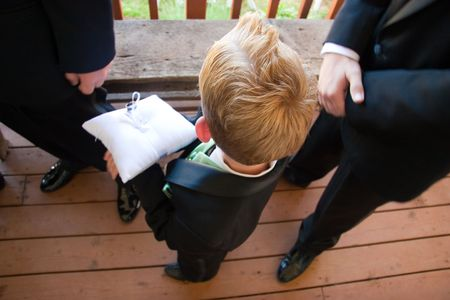 bearer: A young ring bearer holds wedding rings before a wedding ceremony.