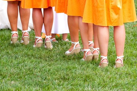 A photo of the feet and legs of bridesmaids during a wedding ceremony. photo
