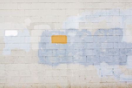 A grey wall has rectangular and square patches of paint used to cover up graffiti and vandalism along the side of an urban building. Stock Photo - 5729720