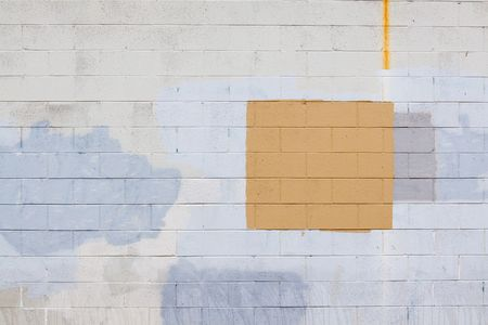 cover up: A grey wall has rectangular and square patches of paint used to cover up graffiti and vandalism along the side of an urban building. Stock Photo