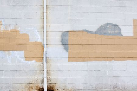 vandalism: A grey wall has rectangular and square patches of paint used to cover up graffiti and vandalism along the side of an urban building. Stock Photo