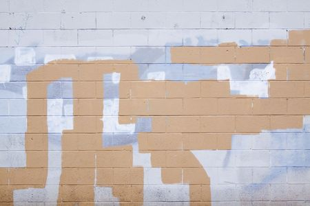 A grey wall has rectangular and square patches of paint used to cover up graffiti and vandalism along the side of an urban building. Stock Photo - 5729723