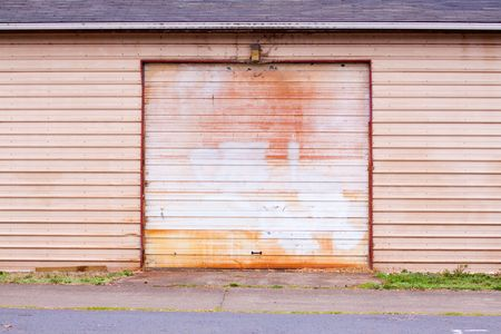 The door of a shed style garage has been painted to cover vandalism and graffiti.