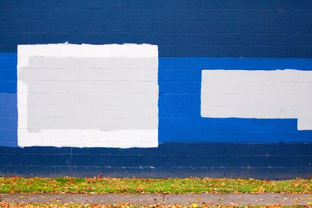 cover up: A dark blue wall of a building next to a street with autumn leaves during the fall that has grey rectangles of paint to cover up graffiti. Stock Photo