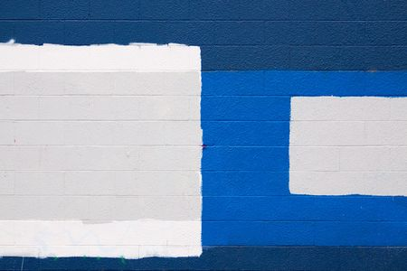 cover up: A dark blue wall with patches of grey and white to cover up graffiti in an urban scene. Stock Photo