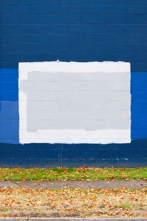 A dark blue wall of a building next to a street with autumn leaves during the fall that has grey rectangles of paint to cover up graffiti. Stock Photo - 5729721