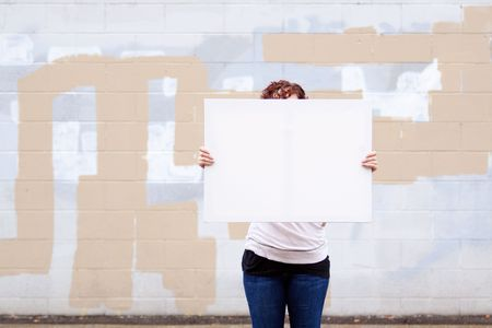 An anonymous girl holds a large white canvas sign with room for text or copy space. Stock Photo - 5796675