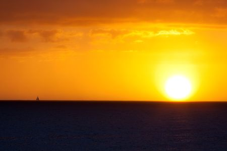 northshore: A sailboat sails offshore during a sunset in Oahu Hawaii along the north shore.