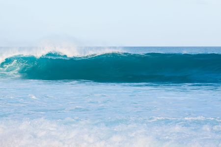 banzai pipeline: Large waves break off the north shore of oahu hawaii during a great time for surfers surfing.
