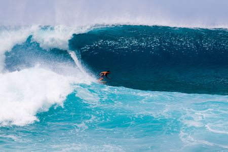 A surfer gets out in front of an enormous wave on the north shore of Hawaii Oahu.