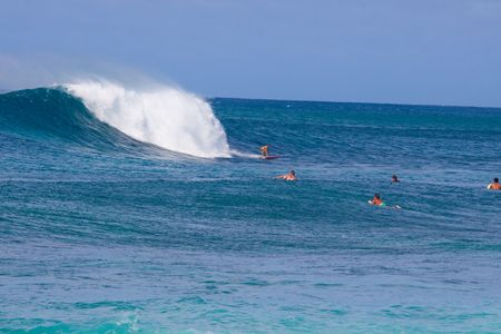 banzai pipeline: Surfers surf some large waves on the north shore of Oahu Hawaii. Stock Photo