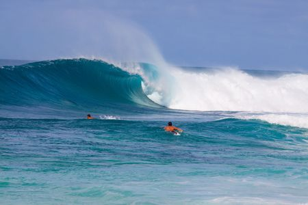 Surfers surf some large waves on the north shore of Oahu Hawaii. 版權商用圖片