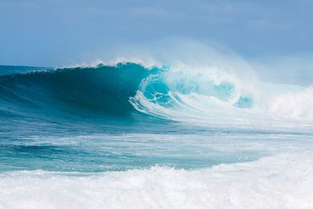 Large waves break off the north shore of oahu hawaii during a great time for surfers surfing.